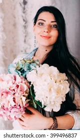 efe87d4d9c Portrait of young brunette woman holding Spring Flower bouquet. Happy  surprised model woman smelling flowers