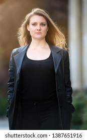 portrait of young brunette woman in leather jacket standing outside