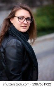 portrait young brunette woman in leather jacket standing outside