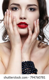 Portrait of young brunette woman on white background. Girl with necklace on the wrist. Female beauty makeup concept.