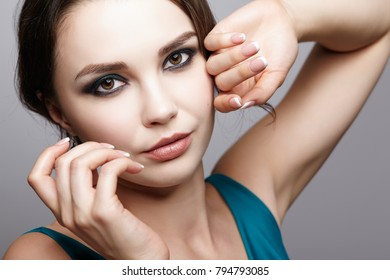 Portrait of young brunette woman on gray background.  Female beauty makeup concept.