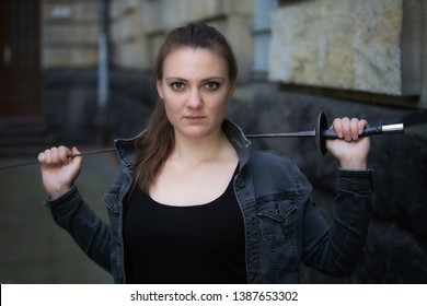 portrait of young brunette woman outdoors with epee