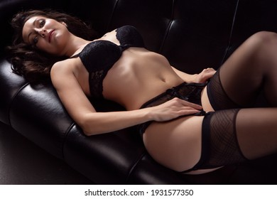 Portrait of a young brunette woman posing in sexy lace underwear on a black leather sofa