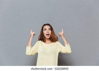 Portrait of a young brunette woman pounting two fingers up at copyspace isolated on the gray background