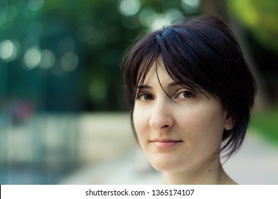Portrait of a young brunette woman with short hair on blurry background
