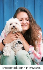 portrait of young brunette woman sitting outdoors with her little dog