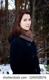 portrait of young brunette woman standing outdoors in the snow