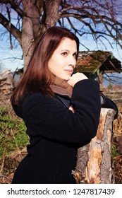 portrait of young brunette woman standing outdoors in the fall
