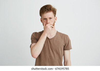 215f43bab66b0 Portrait of young brutal handsome man with beard frowning looking at camera  holding hand on mouth