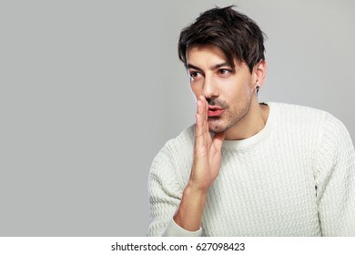 portrait of  young btunette man whispering standing next to color background