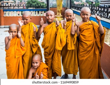 Portrait of young Buddhist scholars with thumbs up in Bhaktapur Durbar square, Nepal. Photo taken on 27 July 2018.
