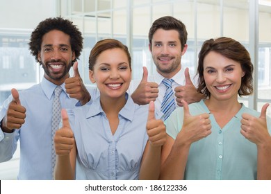 Portrait of young business colleagues gesturing thumbs up in the office