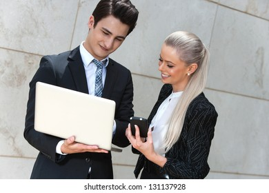 Portrait of young business couple reviewing information.