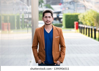Portrait young business handsome man smiling casual with happy outdoor on urban blur background.