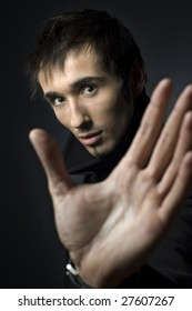 Portrait of a young business man with his hands  on a dark background