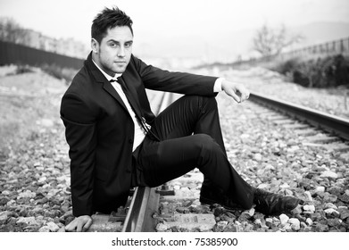 Portrait of a young business man on railway tracks