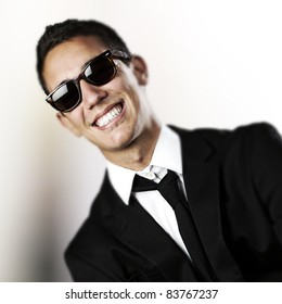 portrait of young business man with suit and sunglasses against a black background