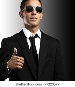 portrait of a young business man with sunglasses with thumb up against a black background