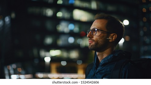 Portrait of an young business man is wearing handsfree earphones in the evening in a city center.