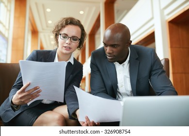 Portrait of young business man and woman sitting in cafe and discussing contract. Diverse businesspeople meeting in hotel lobby reading documents.
