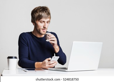 Portrait of a young business man working with laptop computer and drinking coffee