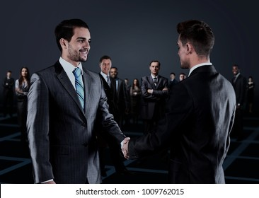 Portrait of young business people. Handshake in front of business people