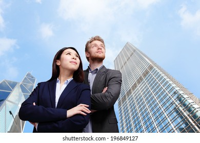 Portrait of young business people looking to the future with city background