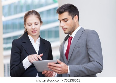Portrait of young business people using a digital tablet