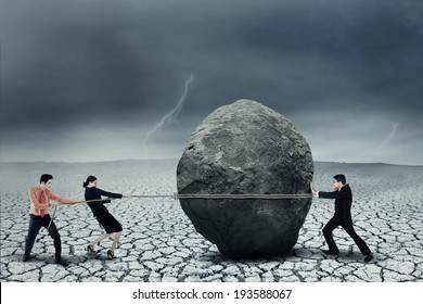 Portrait of young business teamwork try to move the big stone as a big obstacle
