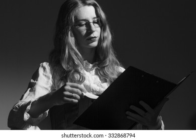 Portrait of young business woman in chair on dark background.