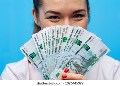 Portrait of young business woman dressed in pink blouse showing money cash fan of russian ruble bills on blue background