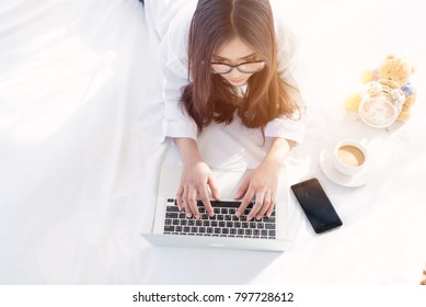 Portrait of a young business woman ,laptop,cup of coffee. Business concept a laptop drinking coffee with her computer on the bed