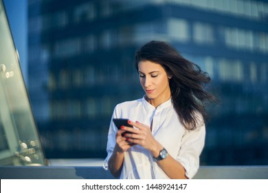 Portrait of young business woman over office buildings holding a smart phone in a hand texting