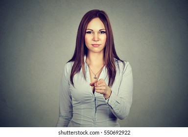 Portrait of young business woman pointing finger at viewer isolated on gray wall background