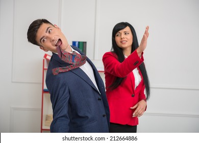 Portrait of young business woman in red jacket  giving a slap in the face to her flirting colleague in office, relationship at work concept