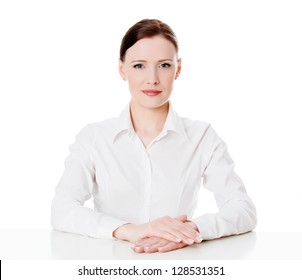 Portrait of a young business woman sitting at a white table, isolated on white