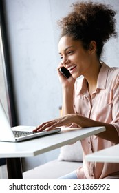 Portrait of a young business woman talking on phone and looking at laptop