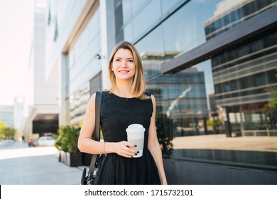 Portrait of young business woman walking to work while drinking takeaway coffee. Business and success concept.