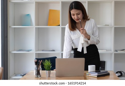 Portrait of young business woman working and thinking in the office