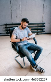 Portrait of young businessman analyzing daily planner and sitting on leather chair indoor