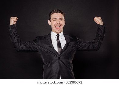 portrait young businessman in black suit with hands up celebrating success. emotions, facial expressions, feelings, body language, signs. image on a black studio background.