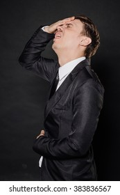 portrait young businessman in black suit hold hands on head. emotions, facial expressions, feelings, body language, signs. image on a black studio background.