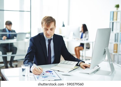 Portrait of young businessman busy working at desk in modern office: checking statistics report and using computer with colleagues in background