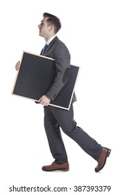 Portrait of a young businessman carrying blackboard while walking.