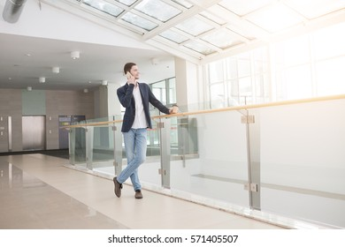 Portrait of young businessman with coffee and smart phone in modern glass office on background. Business man using gadget on his working break