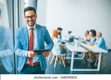 Portrait of young businessman with digital tablet in office