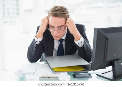 Portrait of a young businessman with documents in front of computer at office desk