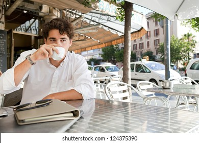 Portrait of a young businessman drinking coffee while sitting outdoors in a coffee shop terrace table with office buildings around in the city.