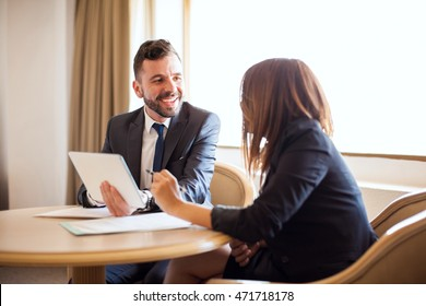 Portrait of a young businessman flirting with a coworker while reviewing some documents together with a tablet computer