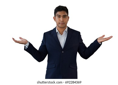 Portrait of young businessman gesturing while wearing suit against white background